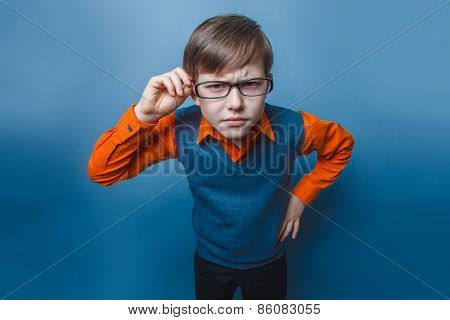 European-looking boy of ten years in glasses frowning, unhappy on a blue background