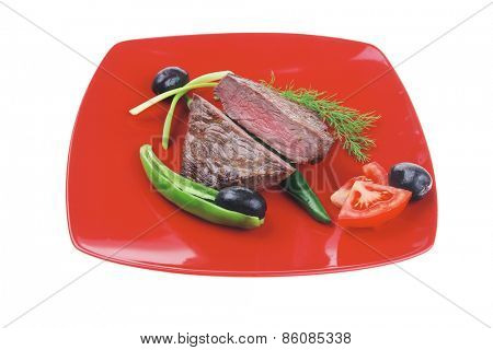 meat savory : grilled beef fillet mignon served on red plate isolated over white background with chili pepper and tomatoes