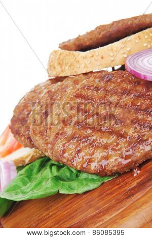 several large roast hamburger with loaf on wooden plate isolated over white background