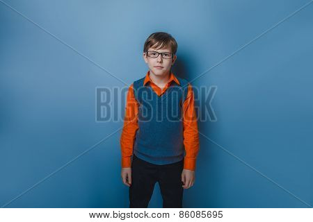 teenager boy with glasses wearing a sweater and a shirt on a blue background