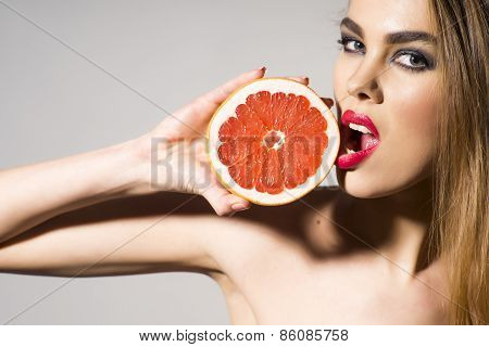 Glamour Girl Holding Grapefruit And Tuoching Him With Lips