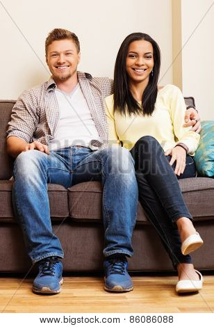 Cheerful multi-ethnic couple sitting on a sofa