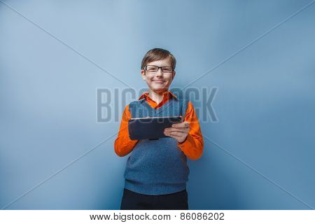 European -looking  boy of ten years in glasses holding tablet in hand on blue background