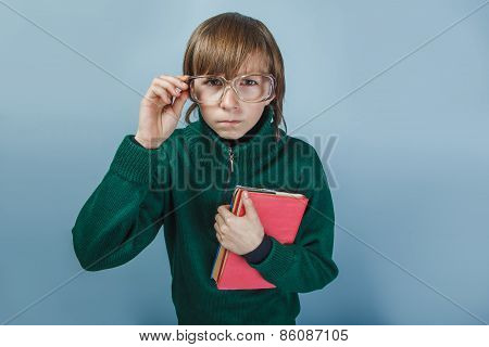 European-looking boy  of ten years in glasses holding a book on a blue background