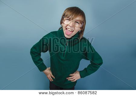 European-looking boy of ten years shows tongue teases on a blue background