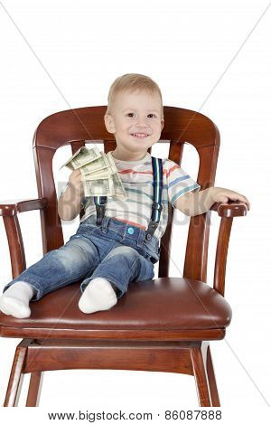 Boy sitting in chair and holding dollars