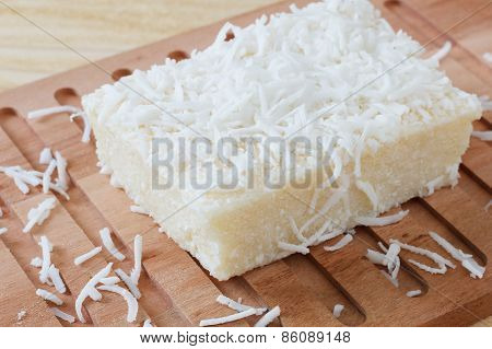 Brazilian  Dessert: Sweet Couscous Pudding (cuscuz Doce) With Coconut On Wooden Cutting Board