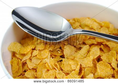 Bunch of corn flake cereals with a metal spoon