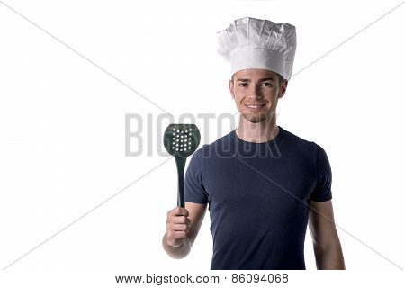 Half Body Portrait Of Young Male Chef Wearing White Hat With Black Ladle On Hand While Looking At Th