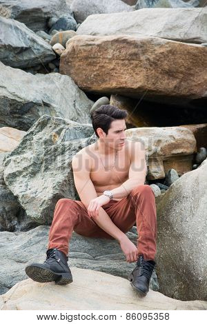 Athletic Shirtless Young Man Sitting Outdoor On Rocks,
