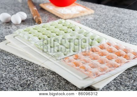 Uncooked ravioli pasta arranged on cutting board at countertop in commercial kitchen