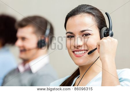 Portrait of confident female customer service executive with colleagues in background at call center