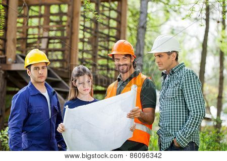 Portrait of confident male architects with colleagues analyzing blueprint at construction site