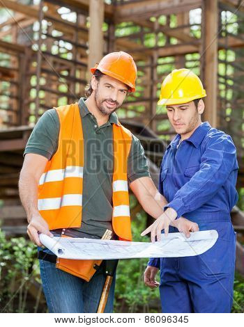 Portrait of confident architect with colleague analyzing blueprint outside incomplete wooden cabin at construction site