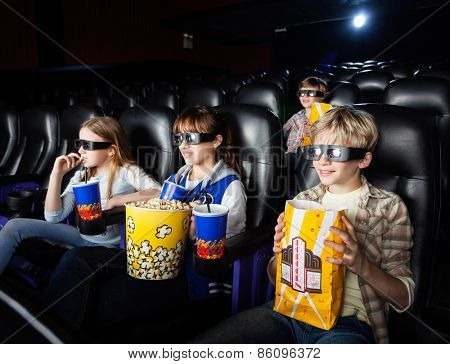 Siblings having snacks while watching movie in 3D cinema theater