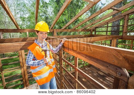 Portrait of smiling female construction worker holding hammer in incomplete timber cabin at site