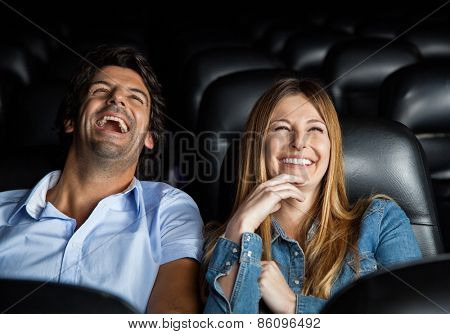 Mid adult couple laughing while watching film in movie theater