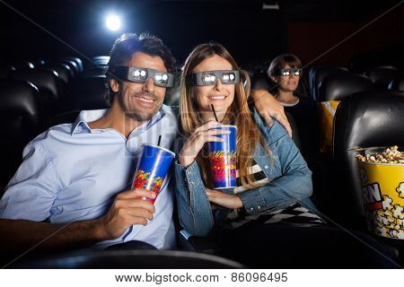 Happy mid adult couple having drinks while watching 3D film in movie theater