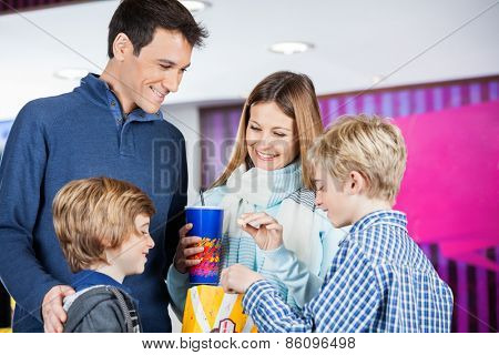 Happy family of four enjoying snacks at cinema