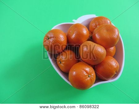 Bowl of clementines on green background