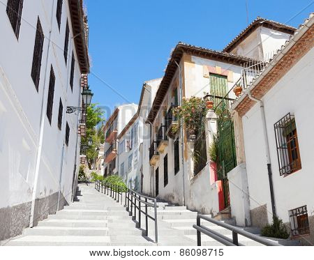 Narrow street with traditional houses  in the old part of Spanish City. Granada, Spain.