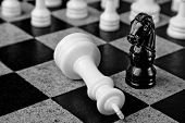 pic of king  - Black knight standing over white king on chess board - JPG