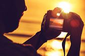 picture of  photo  - Travel Digital Photography Concept Photo with Men Playing His Professional Digital SLR Camera During Sunset.