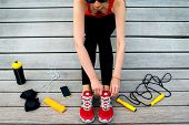 image of jump rope  - Young sport woman tying laces on her sneakers with jump rope - JPG