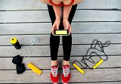stock photo of jump rope  - Sporty woman holding phone with empty screen sitting on the sunbed with jump rope - JPG