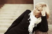 picture of daydreaming  - Young fashion blond woman in black coat daydreaming on the steps - JPG