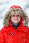 image of down jacket  - Cute boy in a red parka down jacket outdoors on beautiful winter snow day - JPG