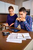 foto of unemployed people  - Unemployed young couple with many debts reviewing their bills. Financial family problems concept.