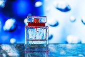 picture of perfume  - Square perfume bottle on blue white and red background with waterdrops - JPG