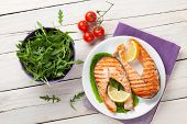 stock photo of salmon steak  - Grilled salmon and salad on wooden table - JPG