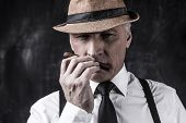 stock photo of suspenders  - Confident senior man in hat and suspenders smelling cigar while standing against dark background - JPG
