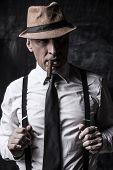 pic of suspenders  - Bossy senior man in hat smoking cigar and adjusting his suspenders while standing against dark background - JPG