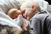 stock photo of brother sister  - A 5 year old big brother is hugging smiling and looking at his newborn baby sister as they sunggle in bed - JPG
