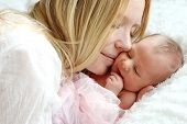 picture of snuggle  - A happy young mother is snuggling her newborn infant daughter in bed - JPG