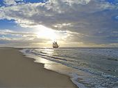 stock photo of brig  - a sailing ship close to the beach in moody sunset - JPG
