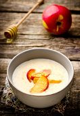 stock photo of porridge  - porridge with caramel apples in a bowl on a wooden table - JPG