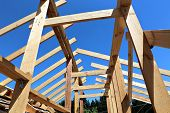 pic of rafters  - Installation of wooden beams at construction the roof truss system of the frame house - JPG