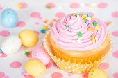 picture of easter candy  - Pink Easter cupcake with candy and sprinkles shallow depth of field - JPG