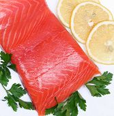 foto of redfish  - Salmon steak with lemon slices and parsley on white plate - JPG