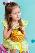 stock photo of hair bow  - Thoughtful little girl with long blond hair wearing pink bow and holding wicker basket with yellow eggs and ribbon sitting on pink chair - JPG