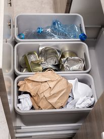 picture of segregation  - Three plastic trash bins in kitchen cabinet with segregated household garbage  - JPG