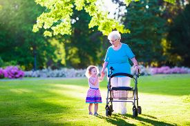 picture of rollator  - Happy senior lady with a walker or wheel chair and a little toddler girl grandmother and granddaughter enjoying a walk in the park - JPG