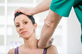 picture of chiropractor  - Chiropractor adjusting neck muscles on female patient - JPG
