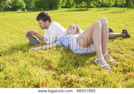 Modern Lifestyle: Relaxing Caucasian Couple Together Outdoors. Joint Leisure Time Reading Ebook And