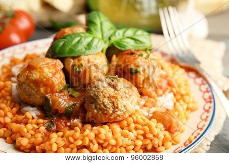 Meat balls with lentil and tomato sauce, wooden spoon on wooden background