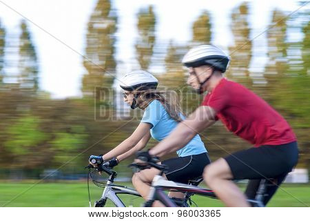 Cycling Concept: Young Caucasian Couple Having A Speedy Bicycle Trip Outdoors. Blurred Motion Due To